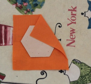 Dab a little glue on paper and attach to the fabric. Do not trim into a hexagon shape. Press.