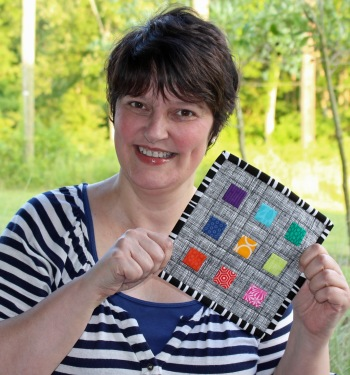 I just received a mug rug from Nina With Freckles as part of a mug rug swap involving individual members of the Modern Quilt Guild.